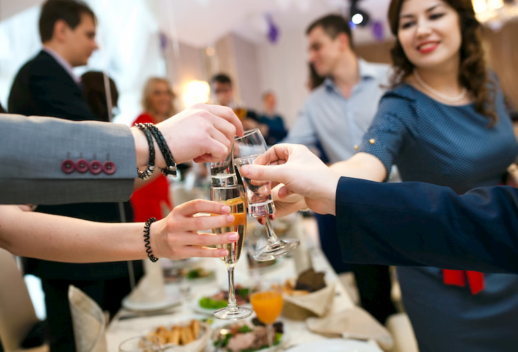 People enjoy champagne and appetizers at a special event.