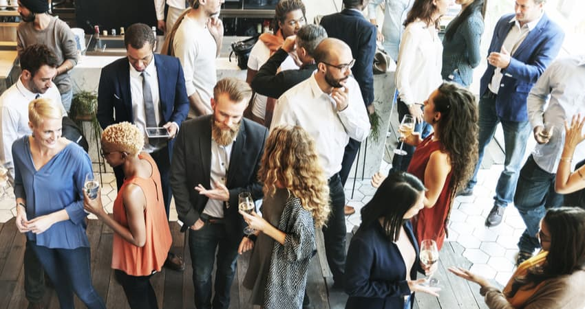 group of businesspeople networking with food and drinks