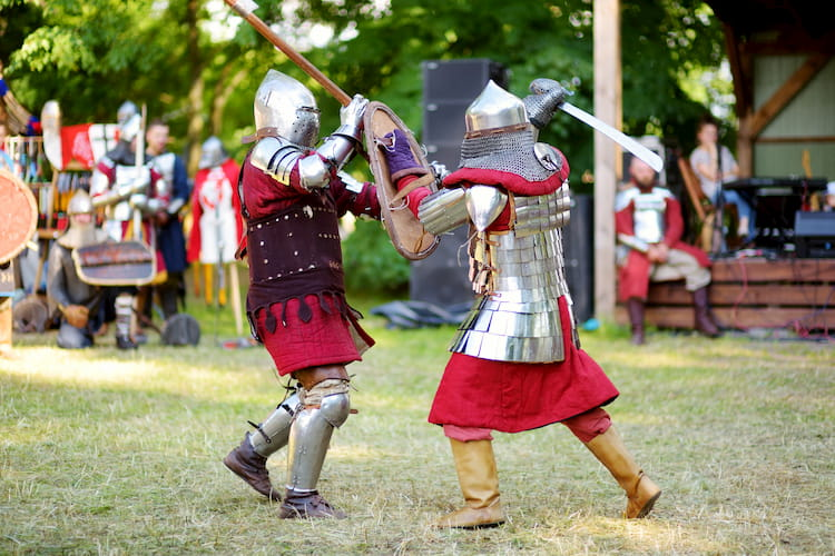 two scarborough renaissance festival visitors swordfight as other patrons watch