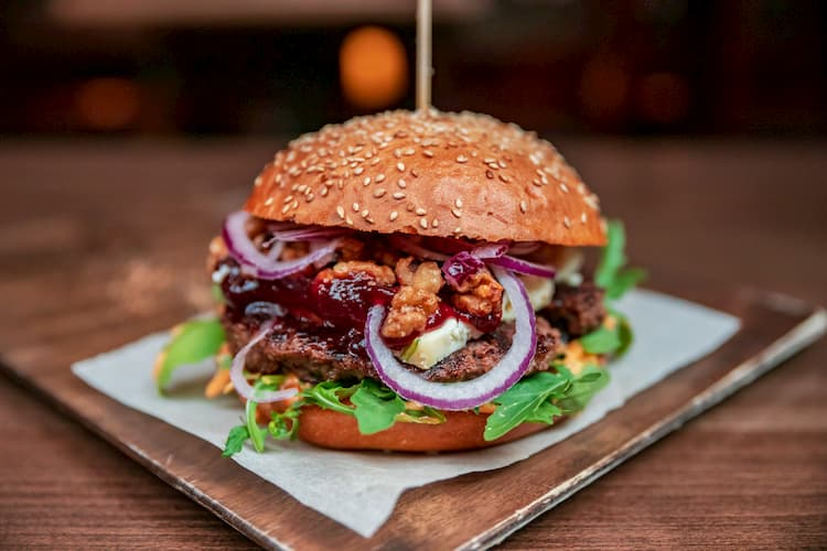 a burger with lettuce, red onions, and condiments held together with a toothpick at chelsea corner