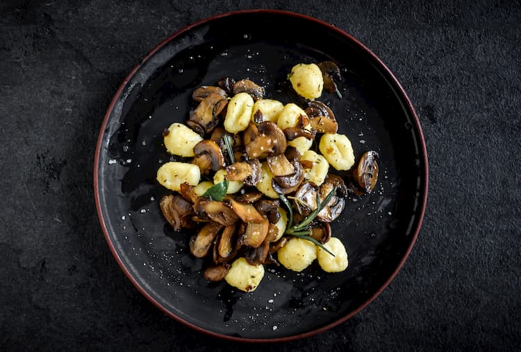 mushrooms and potatoes in a dark bowl with herbs at dolce riviera in dallas