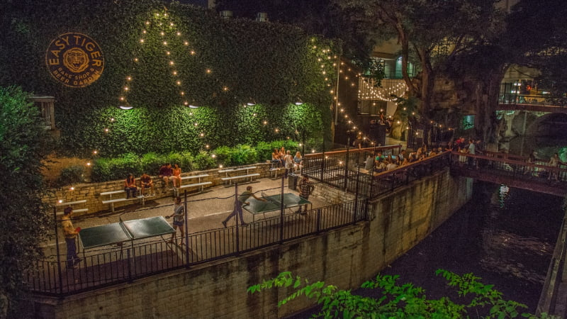 exterior view of Easy Tiger in Austin, TX. Patrons sip beer and play pin-pong under fairy lights on the patio