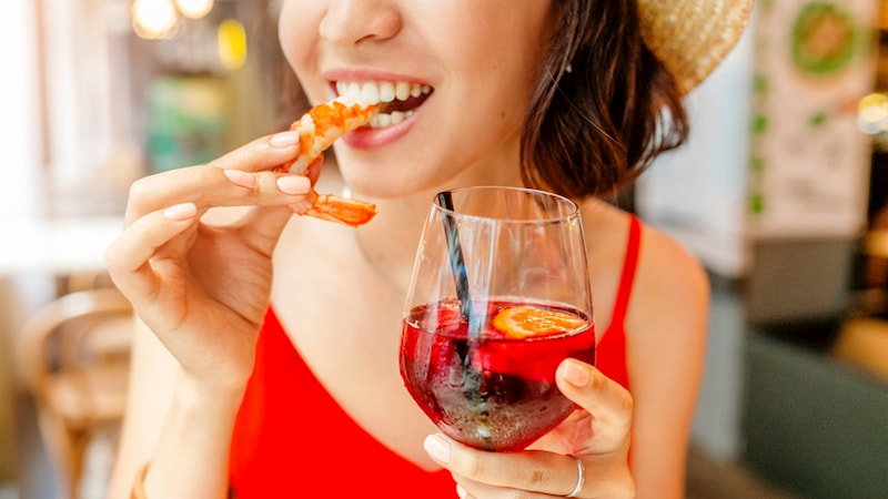 a woman bites into a shrimp and holds a mimosa in a seafood restaurant