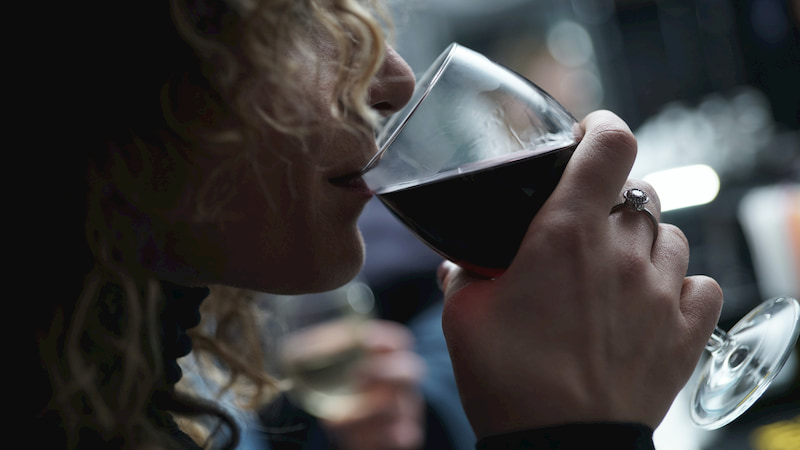 a woman takes a sip of red wine at a darkened restaurant space