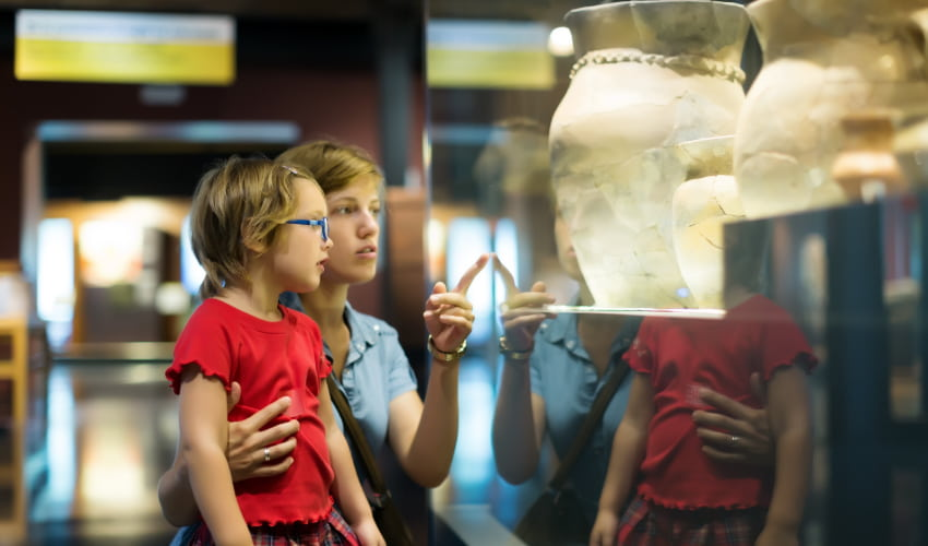 A woman and child examine an ancient vase in a history museum