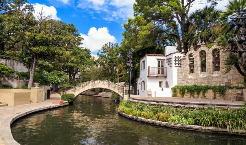 View of an old adobe-style building and stone bridge crossing the San Antonio River in La Villita in San Antonio