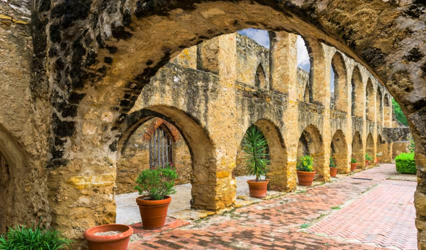 Archways and potted plants in Mission San Jose in San Antonio