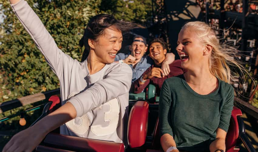 People smiling on a rollercoaster
