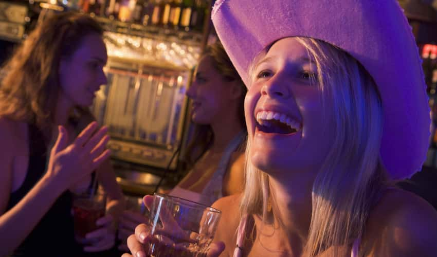A woman in a cowboy hat smiling and drinking with friends at a bar