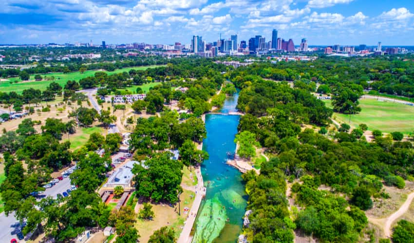 An aerial view of Barton Springs Pool and the Austin skyline