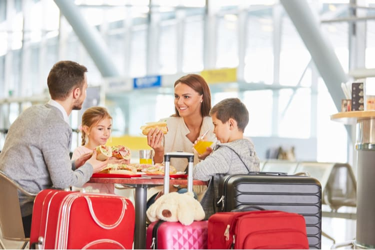 a family eat a meal before their flight