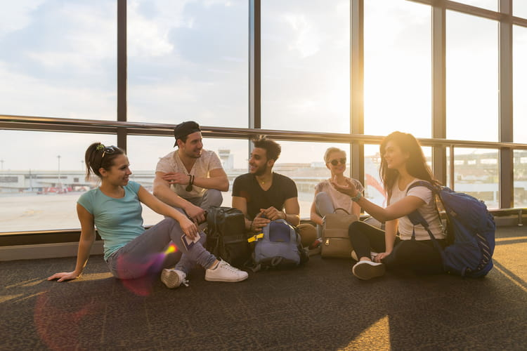 friends sit on the floor near a large window and wait for their flight