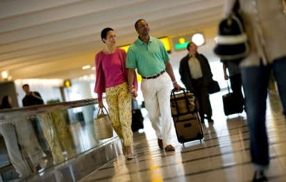 A man and woman hold hands while carrying luggage through an airport