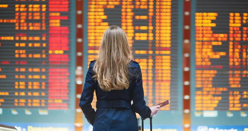 A woman with a suitcase stands in front of a large screen filled with flight information