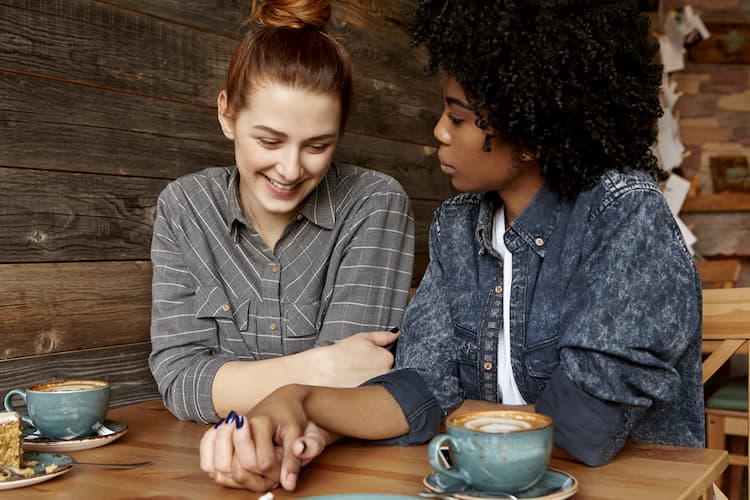 Two women holding hands at coffee shop