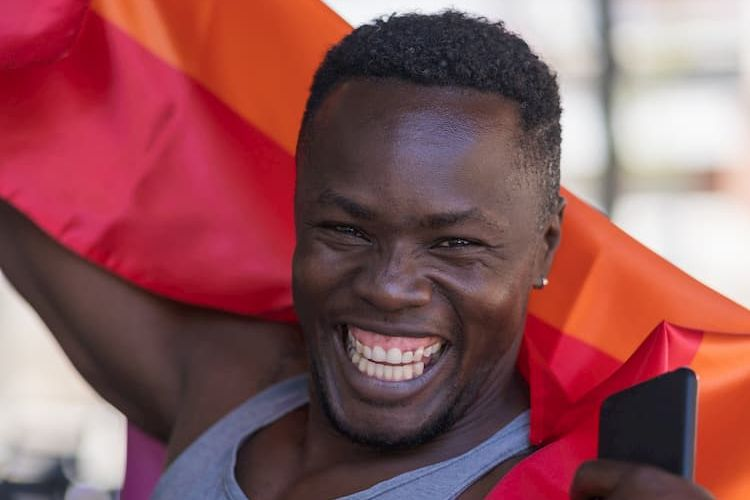 Man smiling with rainbow flag