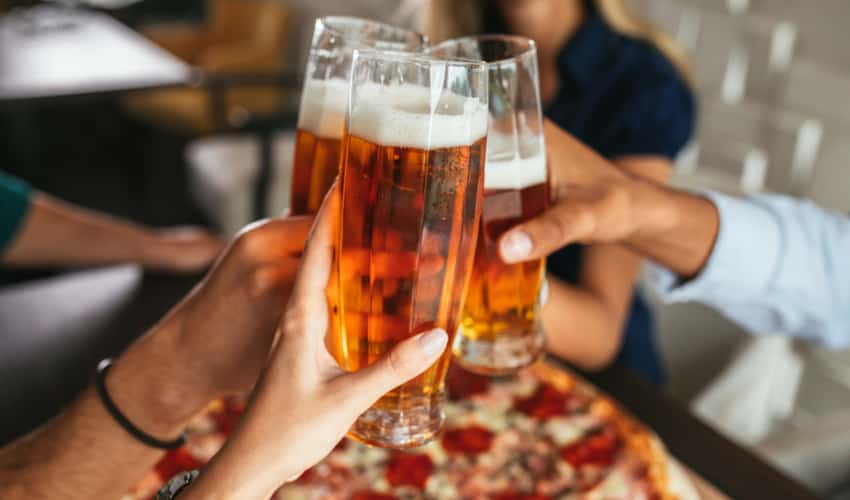 People toasting beer over a pizza