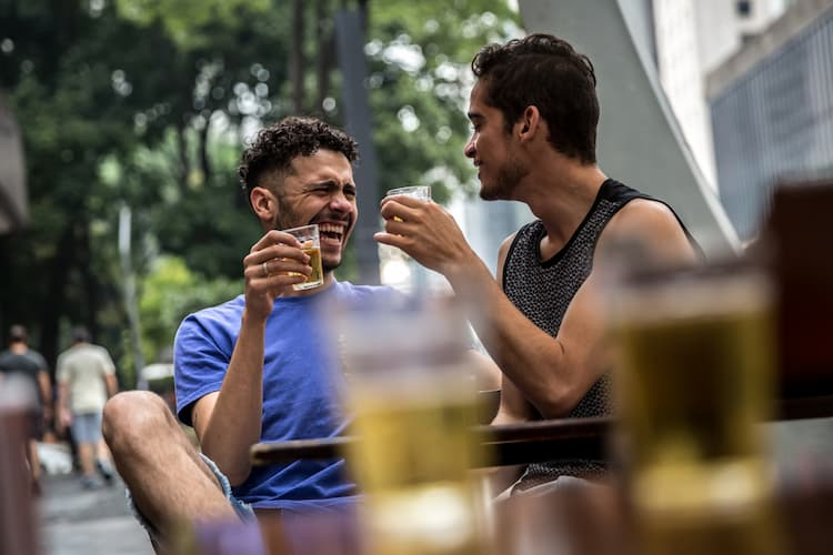 Gay couple drinking beer outside