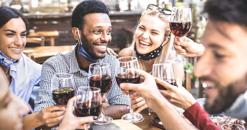 A group of friends toasting wine over a meal outside on a patio