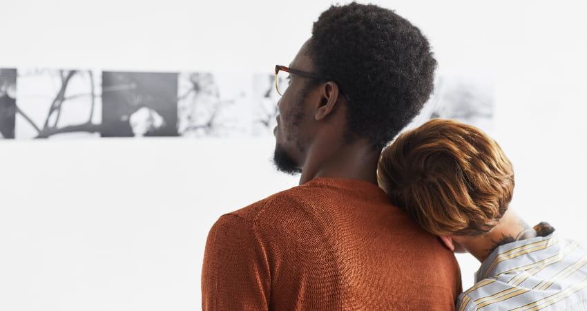 A couple admire a black and white photography exhibition in a gallery
