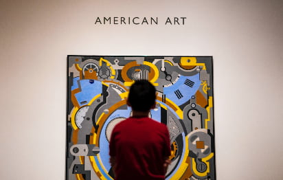A child stands in front of a bright graphic art piece in the Dallas Museum of Art
