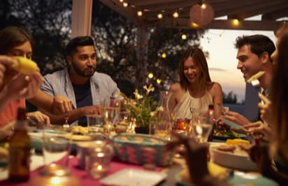 A group of people dining on a patio outside