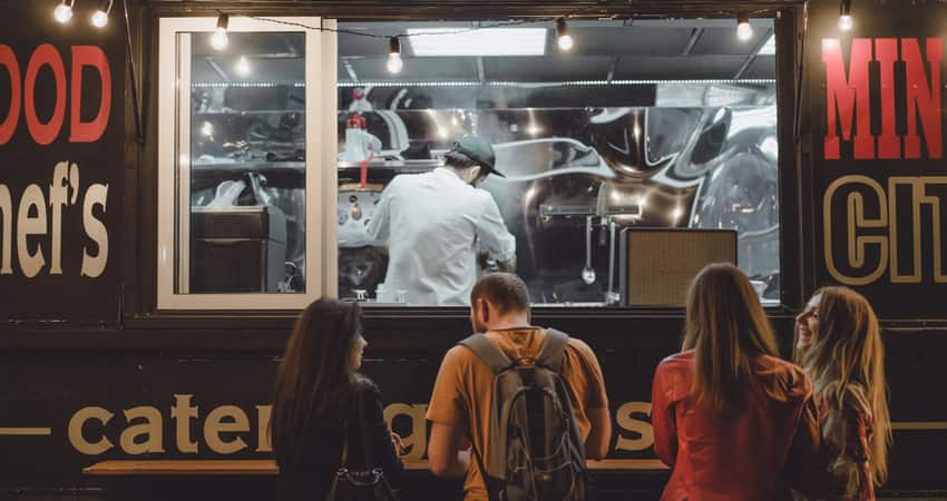 A group of friends waiting in front of a food truck