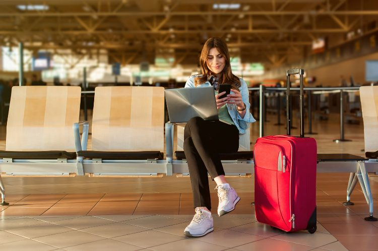 a woman sits with her laptop and checks her phone in an airport lobby