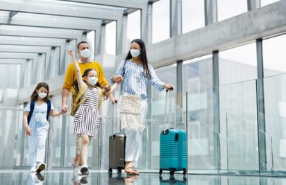 a family walks through an airport with their suitcases