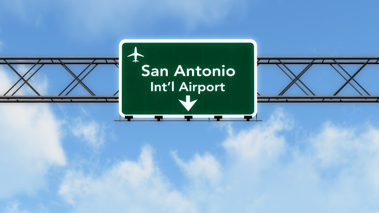 """a sign against a cloudy blue sky that reads """"san antonio int'l airport"""""""