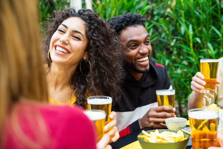 two friends smile and hold their beers while they sit outside