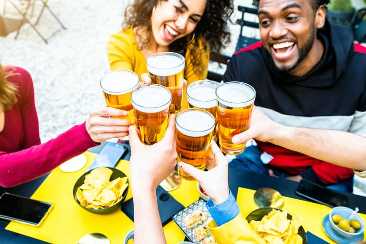 friends smile big and raise their beer glasses for a cheers