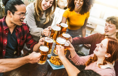 friends cheers their glasses around a table at a brewery