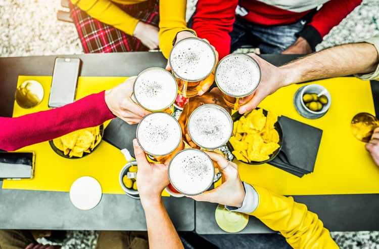 a top view of six friends clinking their beer glasses