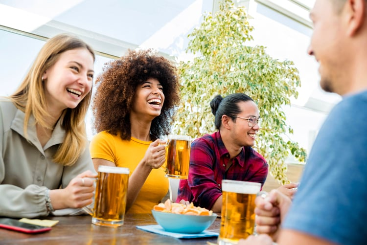 friends laugh as they sit around a table at a brewery