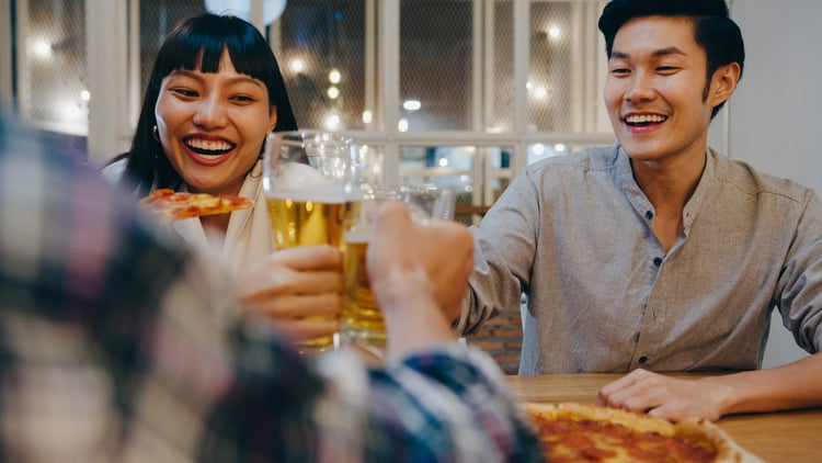 two friends smile at a table while holding pizza and beer