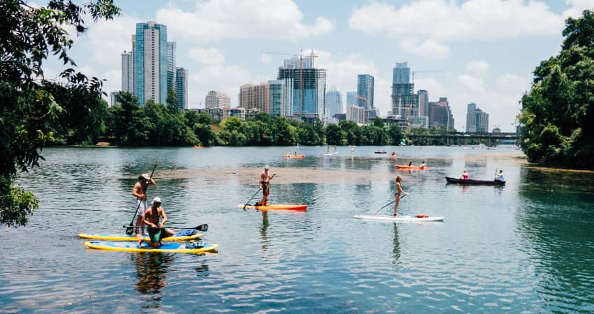 A group of friends paddleboard on a river outside Austin