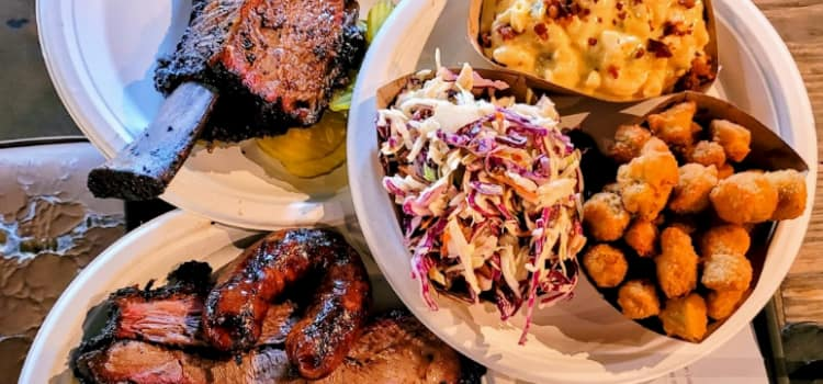 barbecue food arranged in a few plates on a wooden table