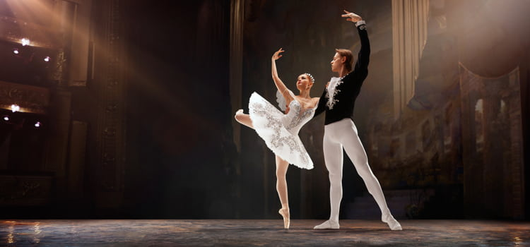 two dancers pose on a well-lit stage