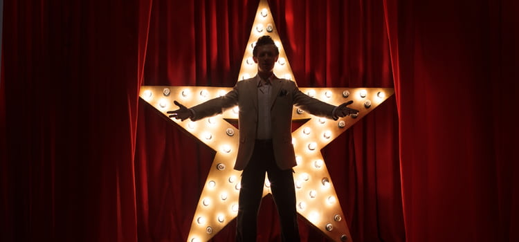 a performer stands with arms out in front of an illuminated star against a red curtain