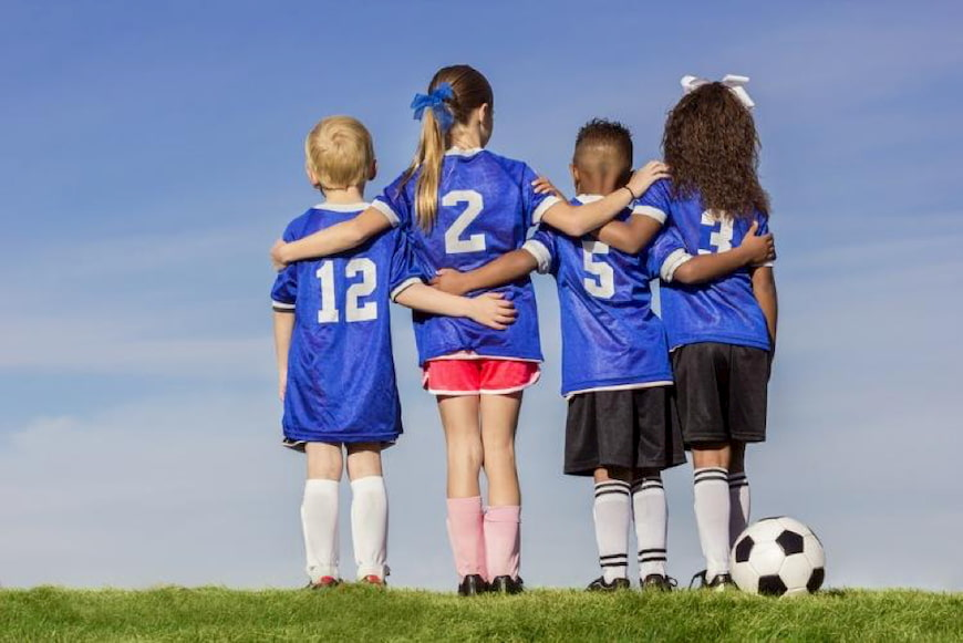 kids stand with their arms around each other after a soccer game